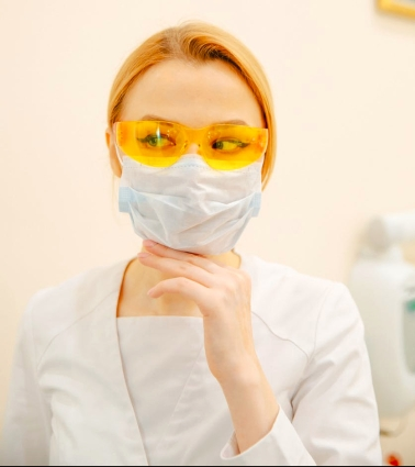 woman in white scrub suit and yellow goggles