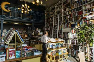 person in white t shirt standing beside books inside a library